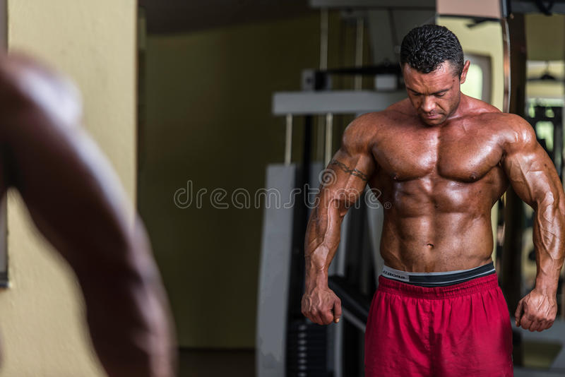 Bez koszuli bodybuilder pozuje przy lustrem obraz royalty free