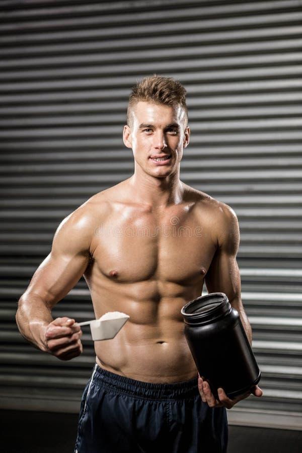 Bez koszuli mężczyzna mienia proteiny proszek obrazy stock