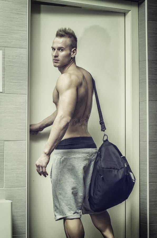 Bez koszuli mięśniowy młodego człowieka otwarcia drzwi z gym torbą, zdjęcie royalty free