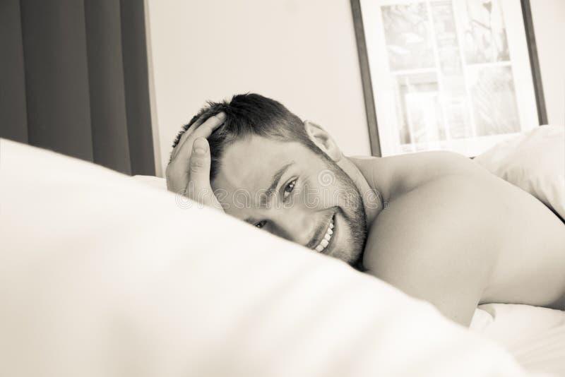Bez koszuli seksowny hunky mężczyzna z brodą kłama nagiego w łóżku obrazy royalty free
