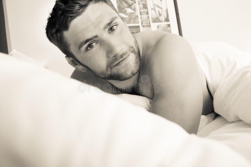 Bez koszuli seksowny hunky mężczyzna z brodą kłama nagiego w łóżku zdjęcia stock