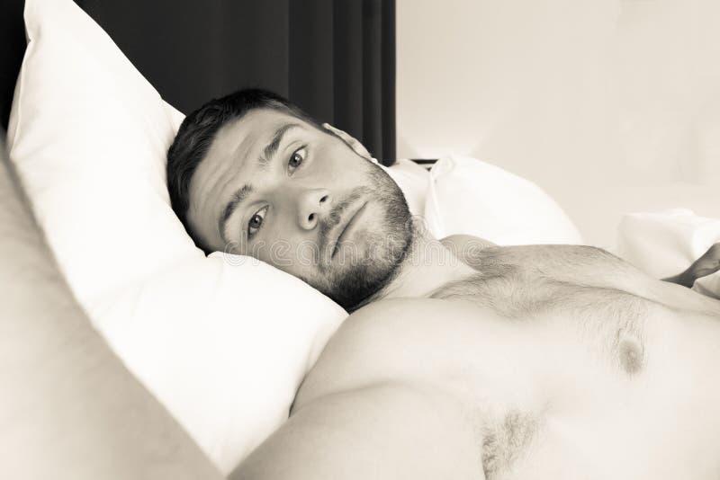 Bez koszuli seksowny hunky mężczyzna z brodą kłama nagiego w łóżku zdjęcie royalty free