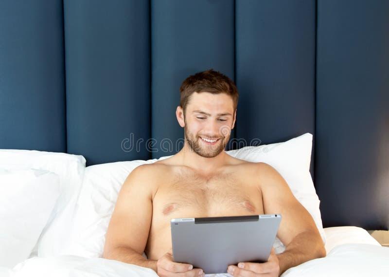 Bez koszuli seksowny hunky mężczyzna z brodą używa ipad pastylkę w łóżku zdjęcie royalty free