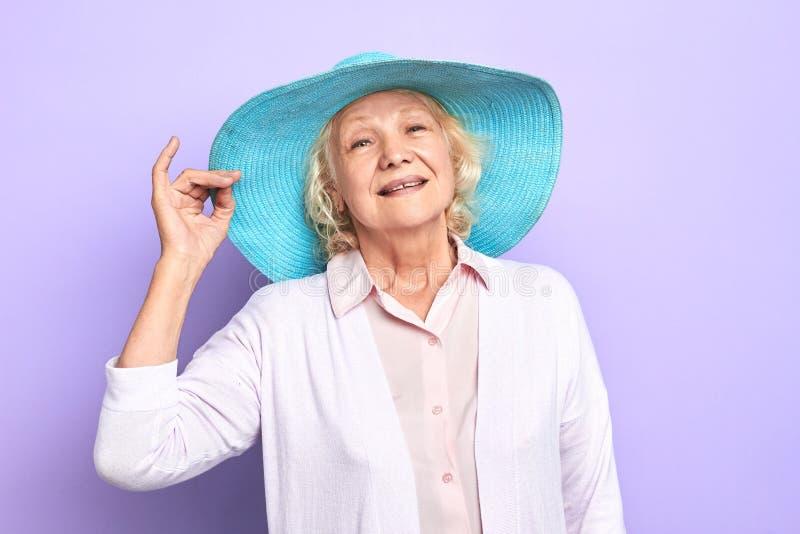 Bezaubern, attraktive alte nette glückliche Frau mit blauem stilvollem Hut lizenzfreie stockfotos