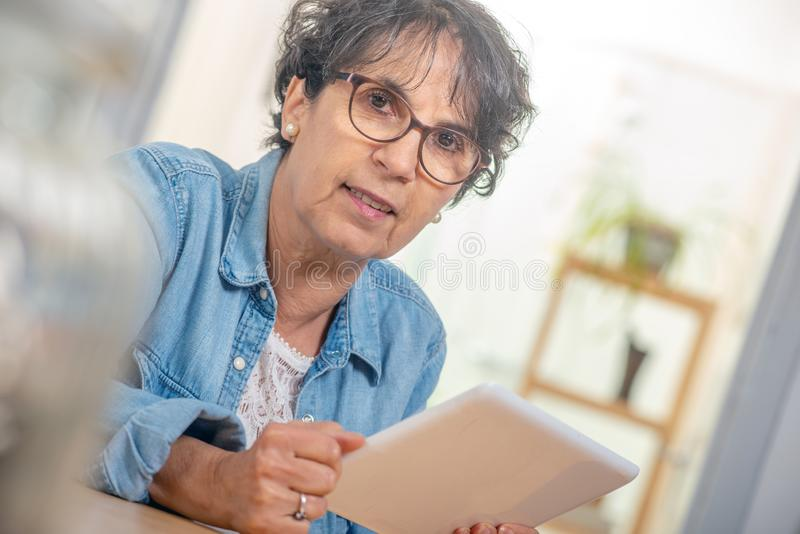 Bezaubernde ältere brunette Frau mit Gläsern unter Verwendung der digitalen Tablette zu Hause lizenzfreies stockbild