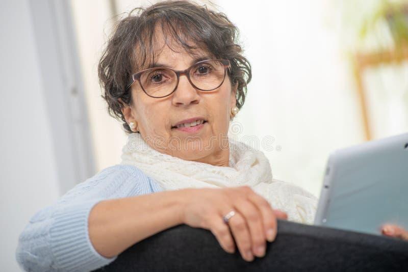 Bezaubernde ältere brunette Frau mit Gläsern unter Verwendung der digitalen Tablette zu Hause stockfoto