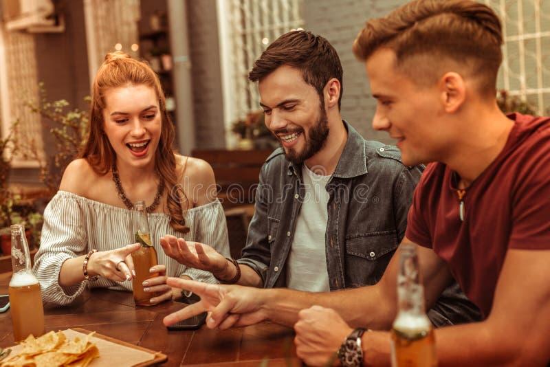 Bezaubernde Dame und Kerle, die an der Bar mit Getränken sitzen lizenzfreies stockfoto