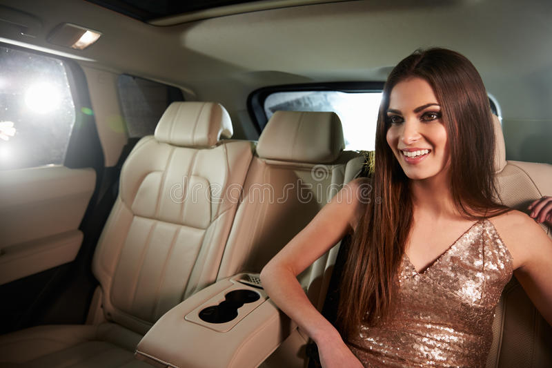Bezaubernde dunkelhaarige junge Frau, die auf der Rückseite einer Limousine sitzt lizenzfreies stockfoto