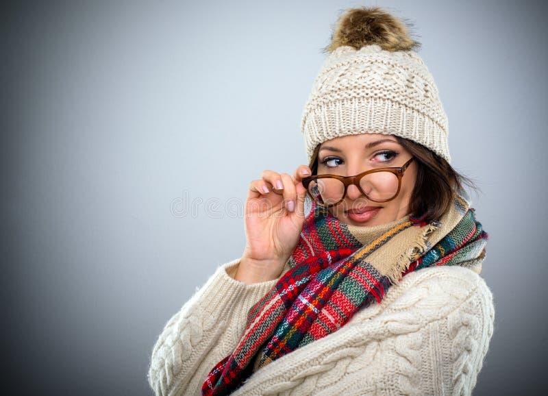 Bezaubernde Frau, die über ihren Gläsern flüchtig blickt lizenzfreie stockfotos