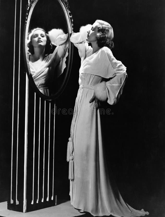 Bezaubernde Frau, die im Spiegel schaut (alle dargestellten Personen sind nicht längeres lebendes und kein Zustand existiert Lief lizenzfreie stockfotos