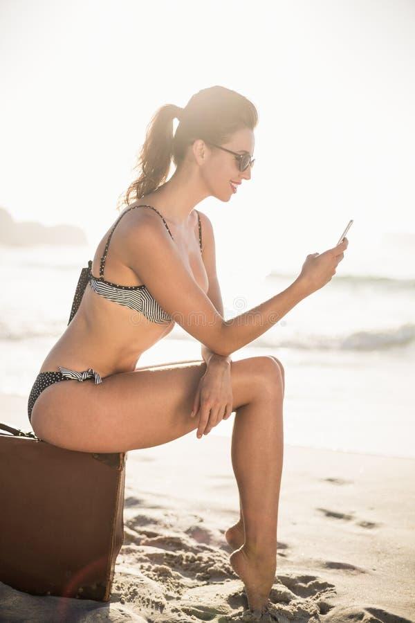 Bezaubernde Frau im Bikinisitzen und im mit Handy lizenzfreie stockfotos