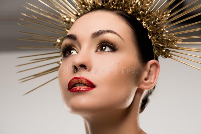 Bezaubernde Frau mit dem Make-up, das goldene Kopfbedeckung trägt lizenzfreies stockbild