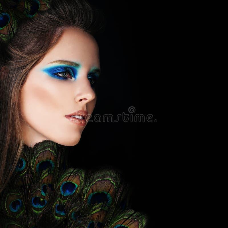 Bezaubernde Frau mit Make-up und Pfau-Federn auf Schwarzem lizenzfreies stockfoto