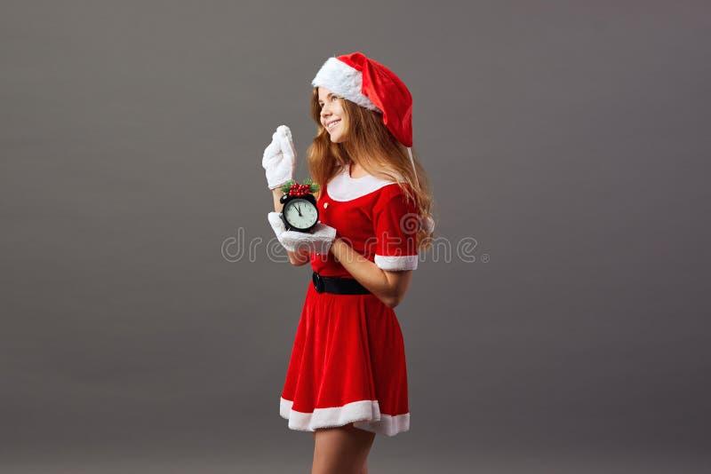 Bezaubernde Frau Santa Claus kleidete in der roten Robe, Sankt Hut an und weiße Handschuhe hält eine Uhr, der fünf zu zeigt lizenzfreie stockfotos