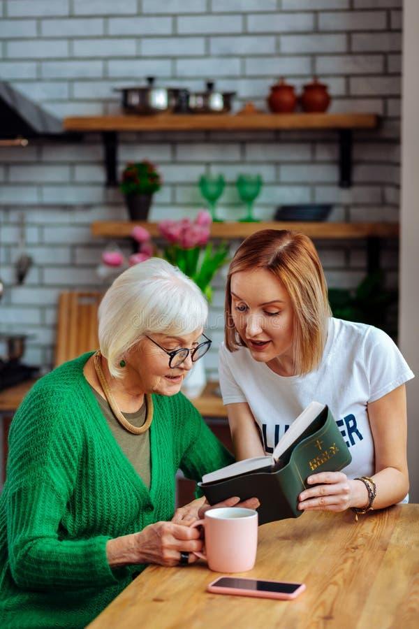 Bezaubernde Freifrau, die bei Tisch und Ablesen der Bibel mit Dame sitzt stockfoto