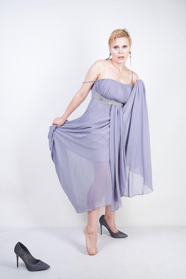Bezaubernde junge Frau der Plusgröße im grauen Kleiderkleid verlor Pantoffel auf weißem Hintergrund im Studio schönes molliges ku lizenzfreies stockfoto