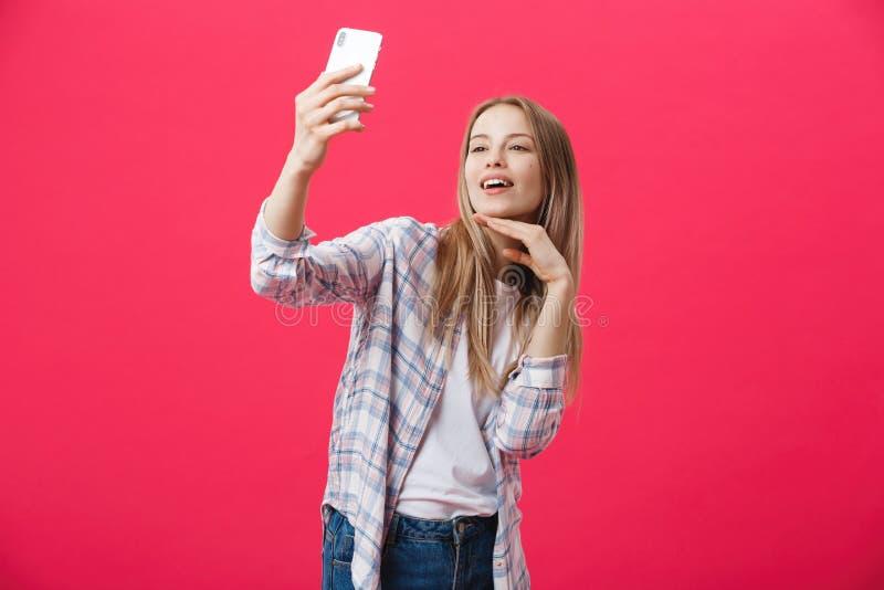 Bezaubernde junge Frau in der weißen Hutreise und selfie auf vorderem Kamera Smartphone nehmen, der auf Glanzrosa aufwirft lizenzfreie stockbilder