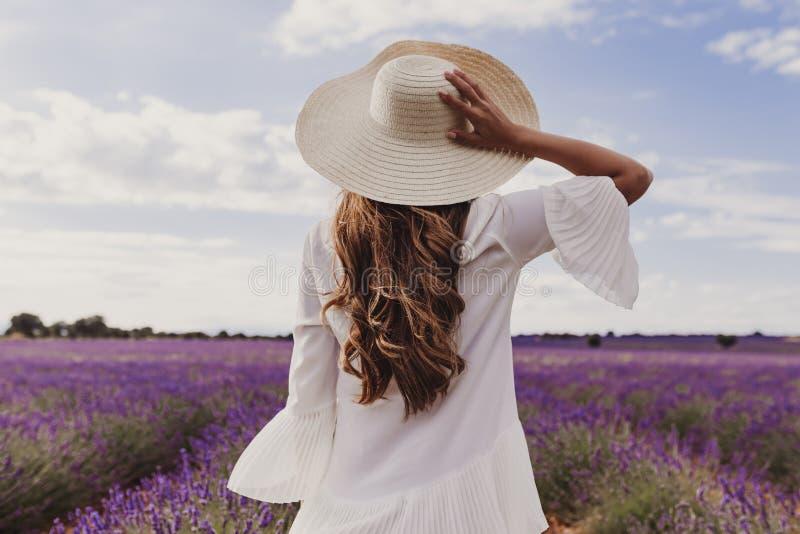 Bezaubernde junge Frau mit einem Hut und einem weißen Kleid auf einem purpurroten Lavendelgebiet bei Sonnenuntergang Lebensstilfr stockfoto