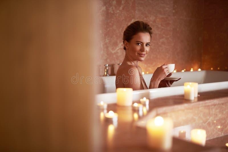 Bezaubernde lächelnde Dame, die Bad mit Tasse Tee nimmt lizenzfreie stockbilder