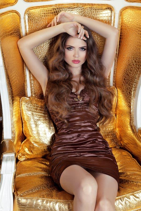 Bezaubernde moderne Frau, die auf Luxusmöbeln aufwirft Schönheit a lizenzfreies stockfoto