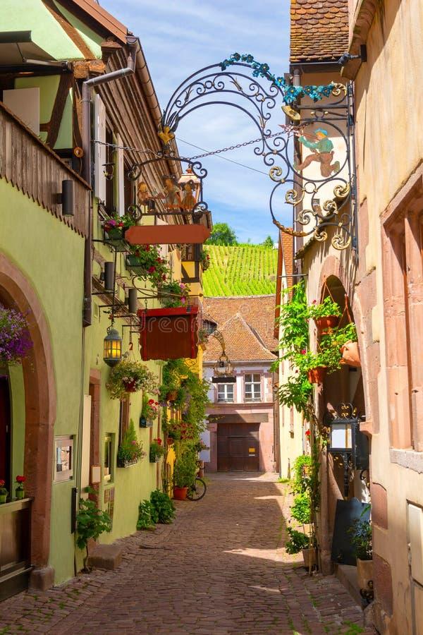 Bezaubernde schmale Straße in Riquewihr in Elsass, Frankreich lizenzfreie stockfotos