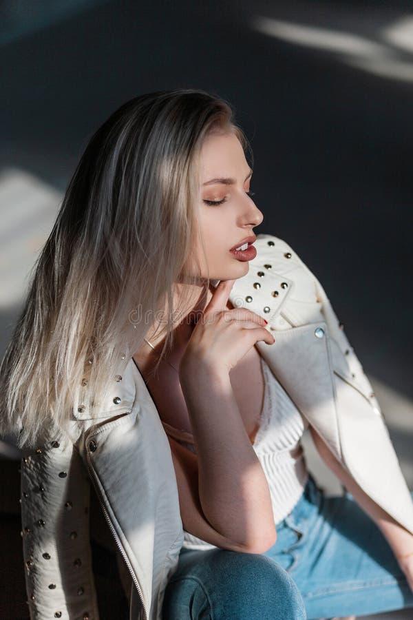 Bezaubernde sexy junge blonde Frau in einer eleganten Lederjacke in den stilvollen Blue Jeans in einem T-Shirt sitzt zuhause stockfoto