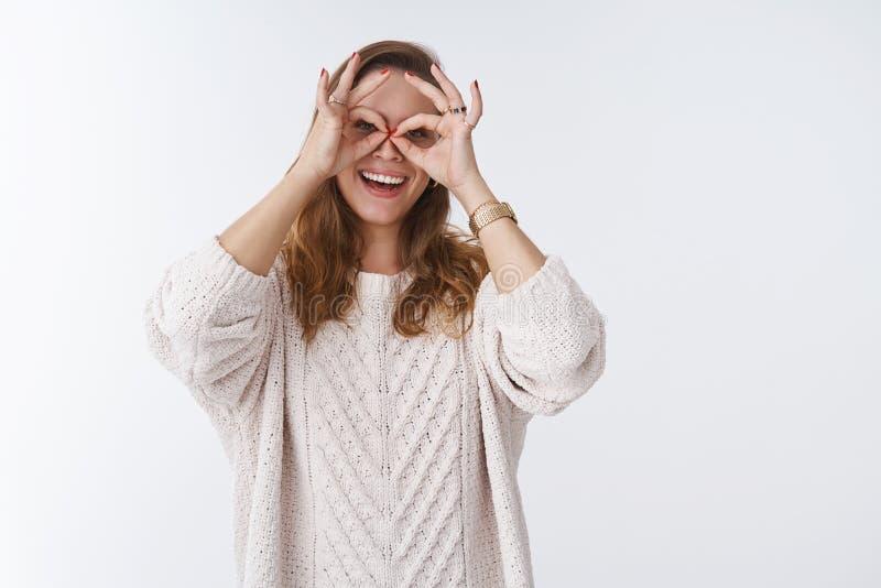 Bezaubernde spielerische charismatische junge sorglose Frau, die den Spaßdummkopf herum zeigt die Schutzbrillen machen Fingergläs stockfotografie