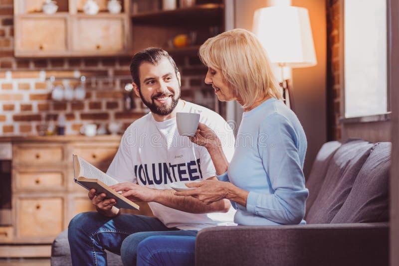 Bezaubernder Freiwilliger, der ein Buch für einen Pensionär liest lizenzfreie stockfotografie