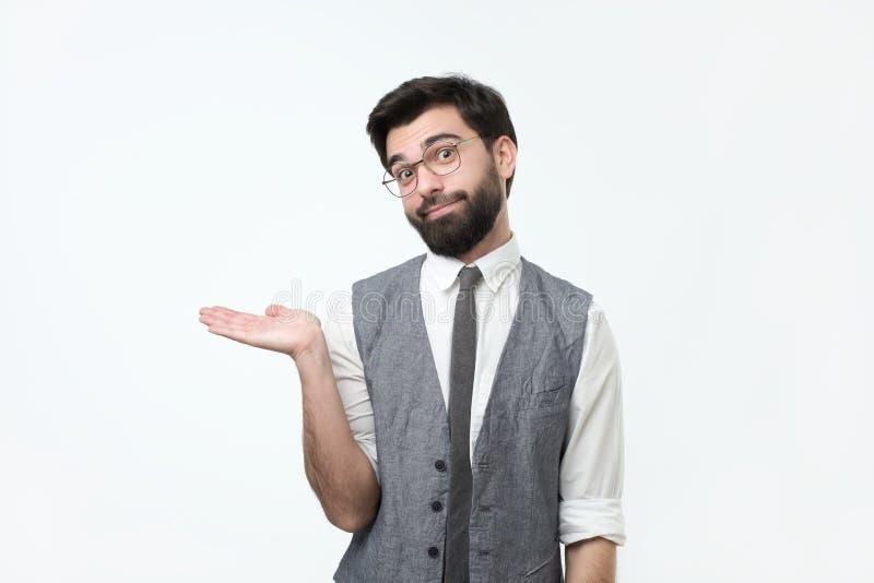 Bezaubernder hübscher junger hispanischer Mann, der seine Hand bis zum anwesenden Verkaufsprodukt der Show hält lizenzfreies stockfoto