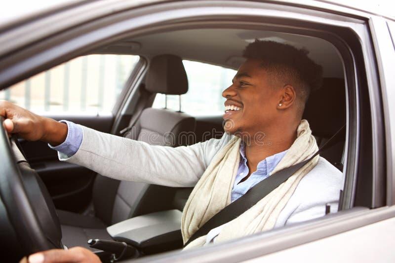 Bezaubernder junger Afroamerikanermann, der Auto in der Stadt fährt stockfoto