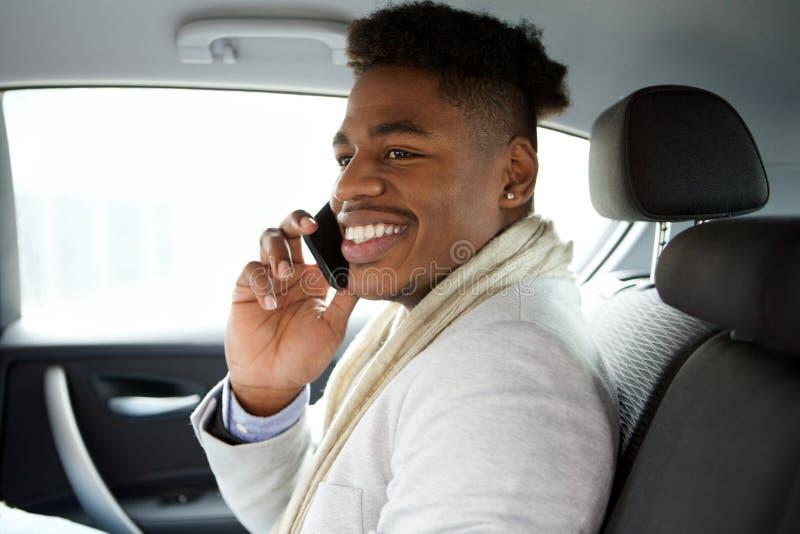 Bezaubernder junger Afroamerikanermann, der im Rücksitze des Autos sitzt und mit Mobiltelefon spricht stockfoto