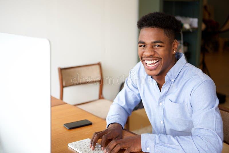 Bezaubernder junger Afroamerikanermann, der mit Computer arbeitet lizenzfreie stockbilder