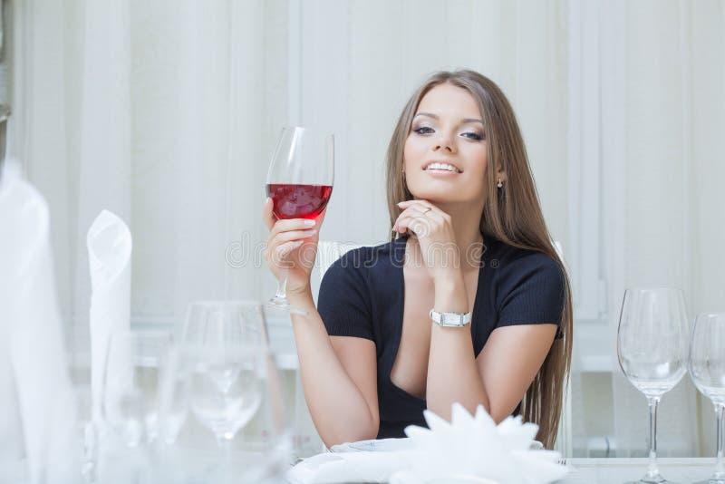 Bezaubernder lächelnder trinkender Wein des Mädchens im Restaurant lizenzfreie stockfotografie