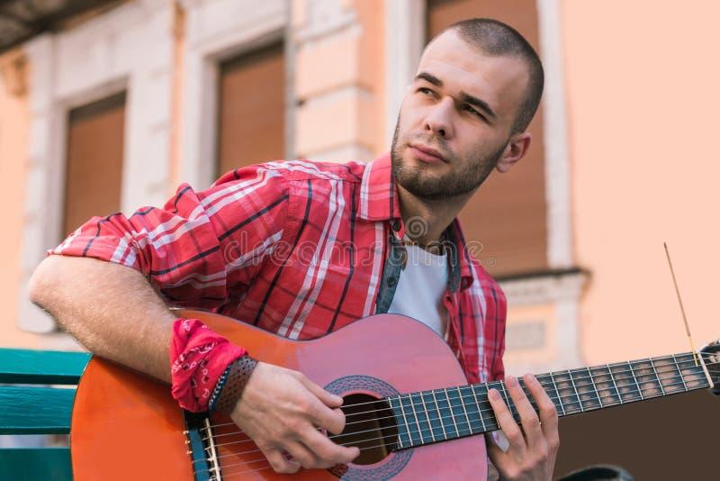Bezaubernder Straßenmusiker, der in der Gitarrenpraxis untertaucht lizenzfreies stockbild
