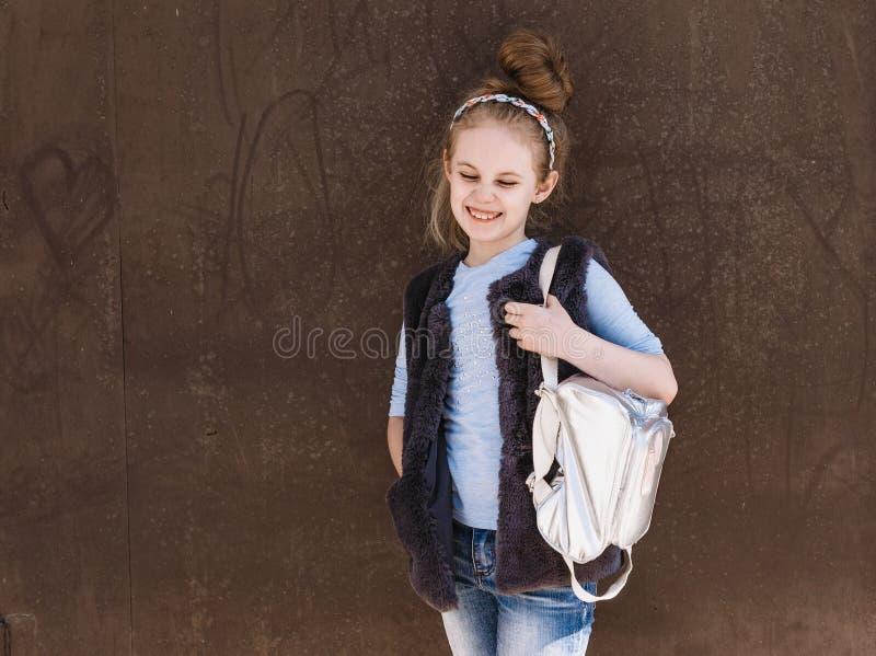 Bezauberndes achtj?hriges M?dchen in einer modischen Ausstattung mit einer Rucksackstellung auf der Stra?e an einem sonnigen Tag stockfotos