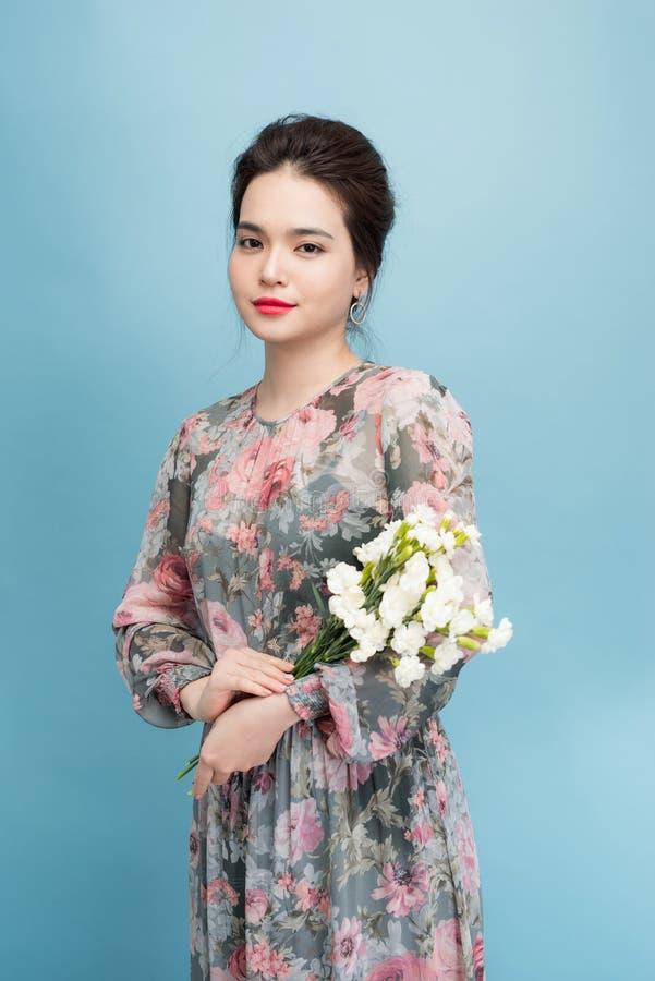 Bezauberndes Asien-M?dchen in der Blumenkleiderstellung auf blauem Hintergrund stockfotos