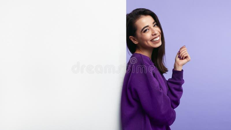 Bezauberndes attraktives Mädchen, stehend neben der leeren weißen Anschlagtafelwand lokalisiert über purpurrotem Hintergrund lizenzfreies stockfoto