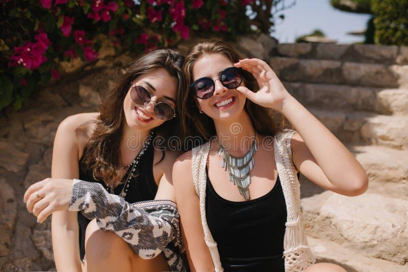 Bezauberndes brunette Mädchen in der Sonnenbrille und in modischer Halskette, die mit ihrer schönen Schwester auf dem Naturhinter stockfotos