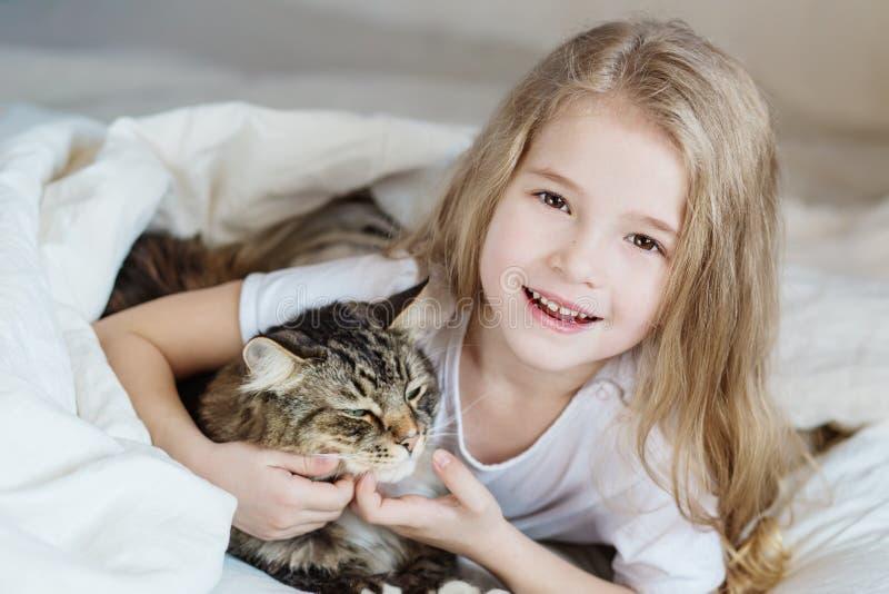 Bezauberndes glückliches kleines Mädchen, das ihre Katze umarmt lizenzfreies stockfoto