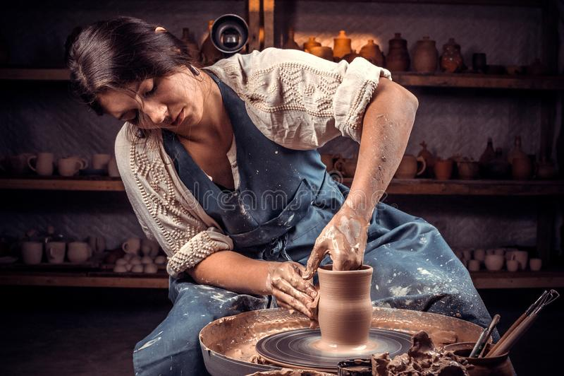 Bezauberndes handicraftsman zeigt, wie man mit Lehm und Töpferscheibe arbeitet Herstellung von keramischen Tellern stockfotos