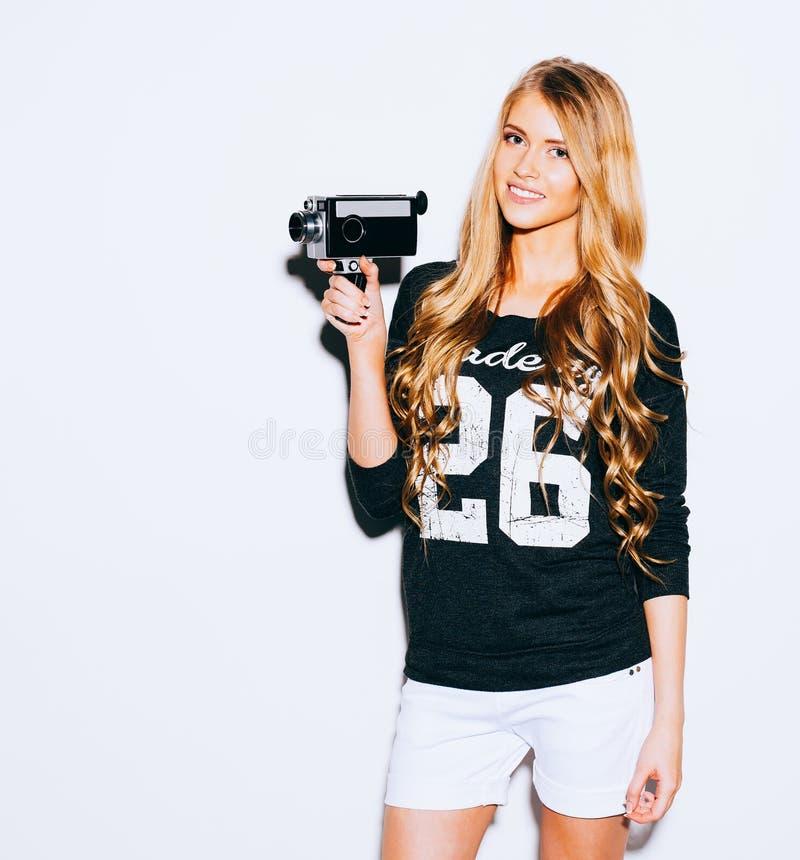 Bezauberndes Hippie-Mädchen des Porträts mit altem Weinlesekino 8 Millimeter-Kamera, die einen Film auf weißem Hintergrund schieß stockfotos