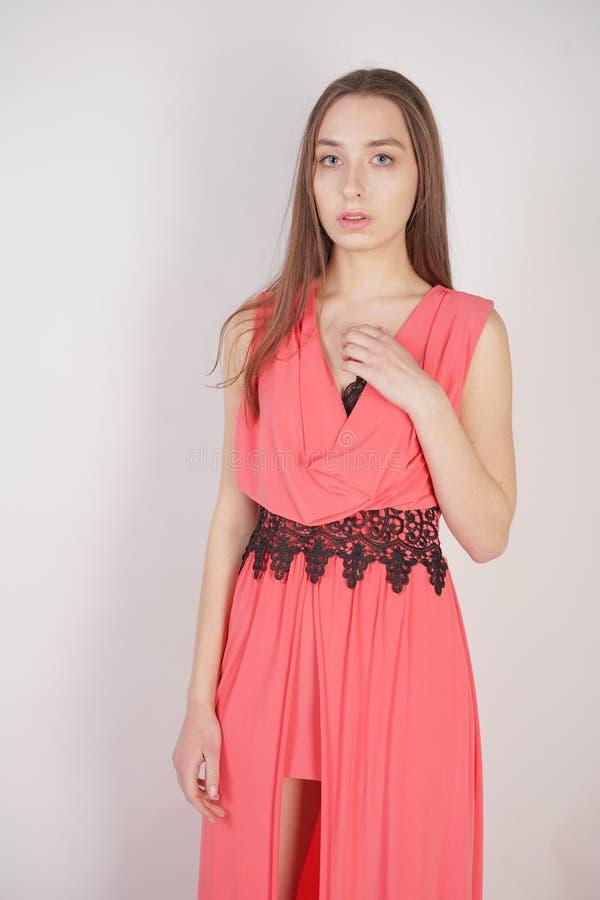 Bezauberndes junges Mädchen im roten glättenden langen Kleid mit schwarzen Spitzeständen auf einem weißen Hintergrund im Studio stockbilder