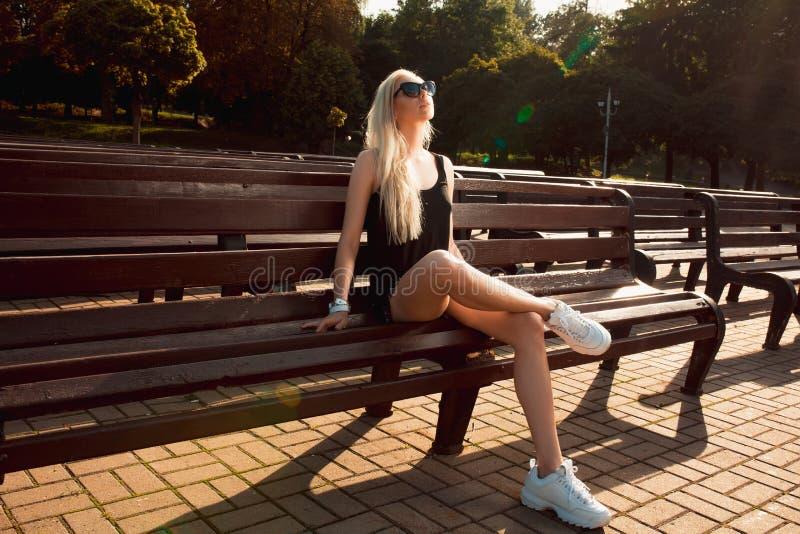 Bezauberndes junges Modell im zufälligen Kleid und in weißem Turnschuhe posin lizenzfreie stockfotografie