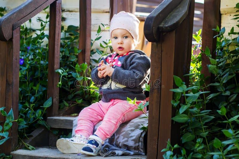 Bezauberndes kleines Baby sitzt auf hölzernen Schritten unter grünen Sträuchen stockbild