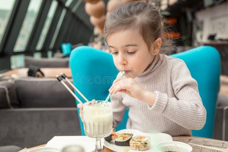 Bezauberndes lustiges kleines Mädchen trinkt ein Milchshaken in einem Restaurant lizenzfreie stockfotos