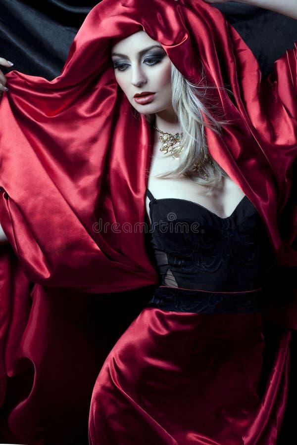 Bezauberndes Mädchen in der roten Robe stockfoto