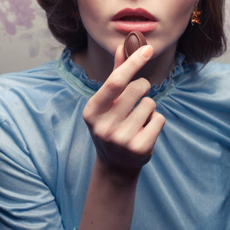 Bezauberndes Mädchen im blauen Kleid Schokoladenbonbon essend stockfotografie