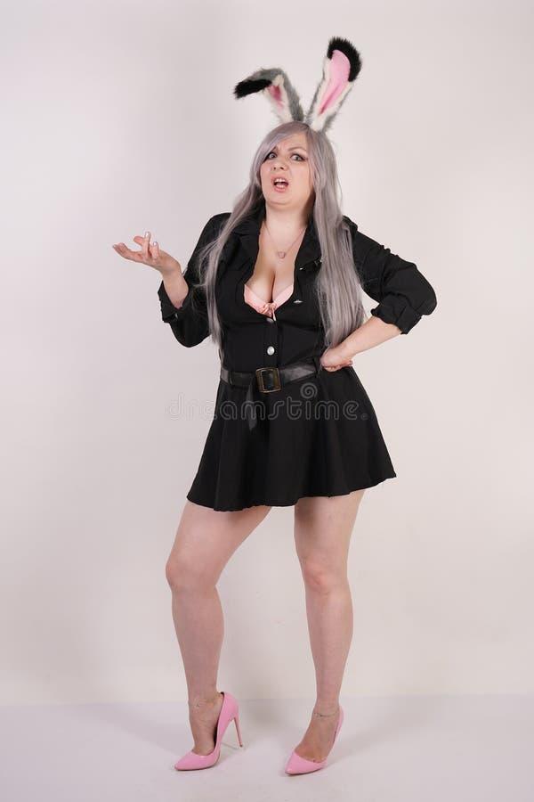 Bezauberndes molliges Mädchen im Polizeikostüm mit den cosplay Hasenohren sehr emotional und verärgert auf weißem Hintergrund stockfotografie