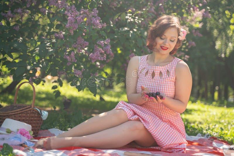 Bezauberndes Pinupmädchen genießt einen Rest und ein Picknick auf dem grünen Sommergras kaukasische Frau der hübschen Weinleseart stockfotos