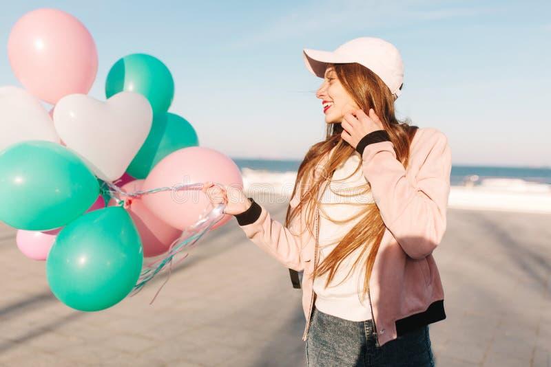 Bezauberndes schlankes Mädchen in einer Kappe untersucht durchdacht den Abstand und das Lächeln und hält ein Bündel Ballone Portr stockfotografie